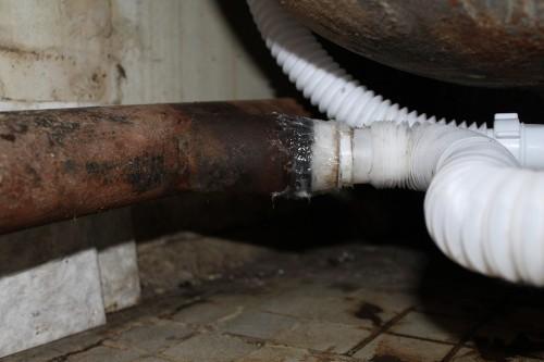 Соединение чугунной трубы с пластиковой, покрытое герметиком
